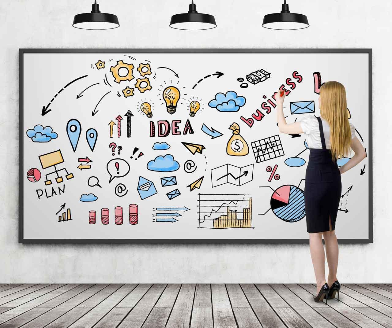 pourquoi avoir un site internet : une jeune femme blonde dessine des icons relatifs au business. Image pour l'article : pourquoi avoir un site internet du site Jdesign.fr