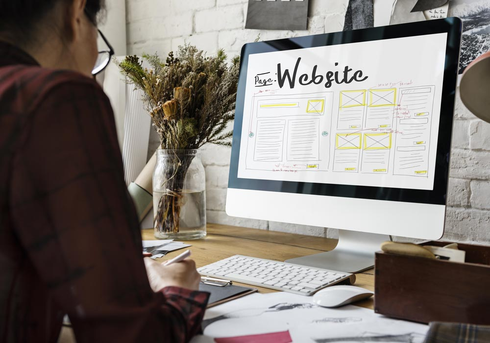 Portfolio clients de l'agence web. un ordinateur de type imac sur un bureau. une personne travaille sur une maquette webdesign.