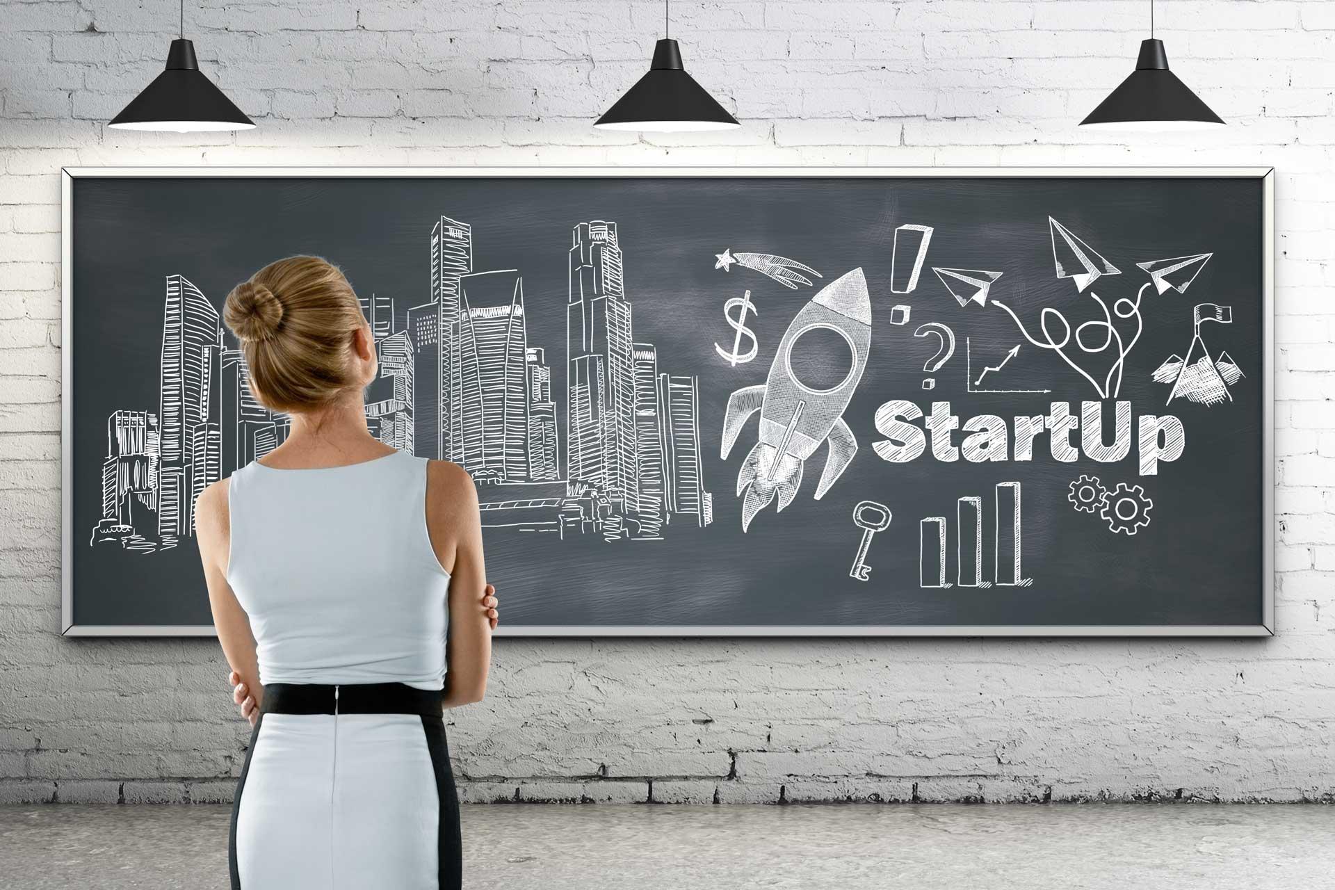image de fond pourquoi avoir un site internet. une jeune femme blonde regarde un tableau en ardoise avec des dessins lier au mot star-up