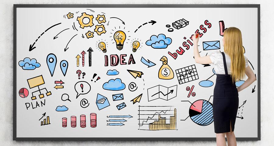 Image pour l'article : pourquoi avoir un site internet du site Jdesign.fr ; une jeune femme blonde dessine des icons relatifs au business.